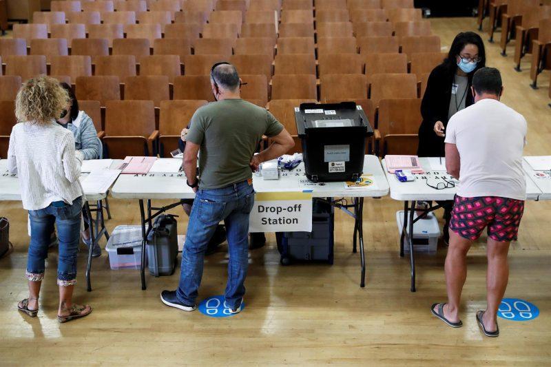 ELECCIONES. Las personas se registran con los trabajadores electorales antes de emitir sus votos en Sherman Oaks, California, el 14 de septiembre de 2021. | Foto: Efe.
